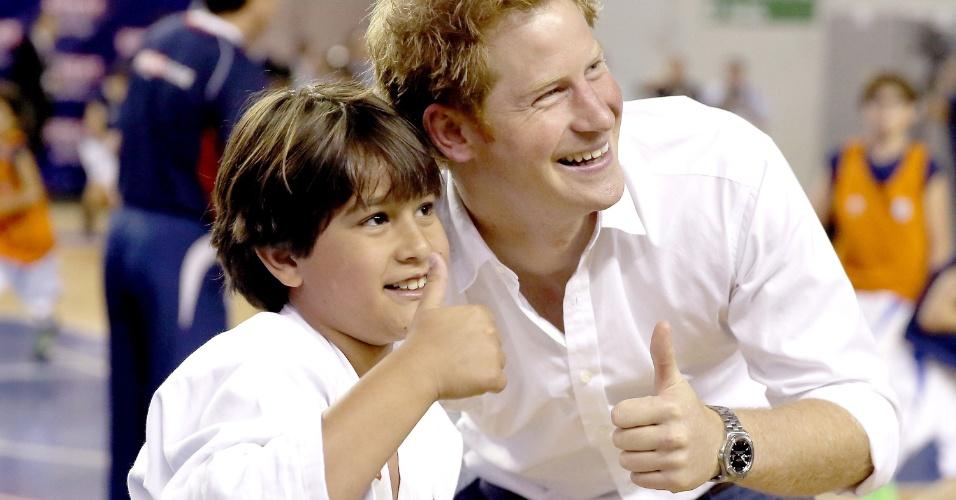 24.jun.2014 - Simpático, Príncipe Harry posa com aluno de judô do Minas Tênis Clube, em Belo Horizonte