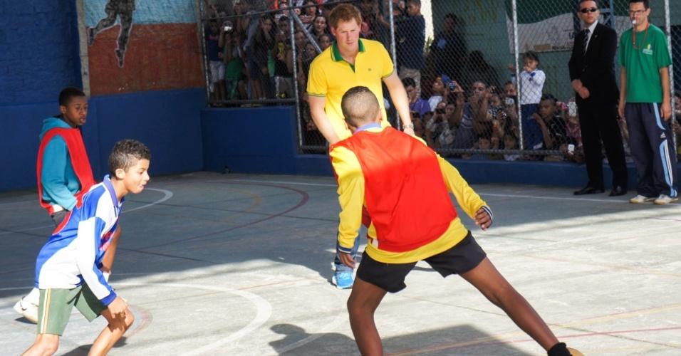 25.jun.2014 - Com a camisa do Brasil, Príncipe Harry joga futebol com crianças de projeto social em Diadema. Usando calça jeans e tênis, ele arriscou uns dribles em quadra na cidade paulista