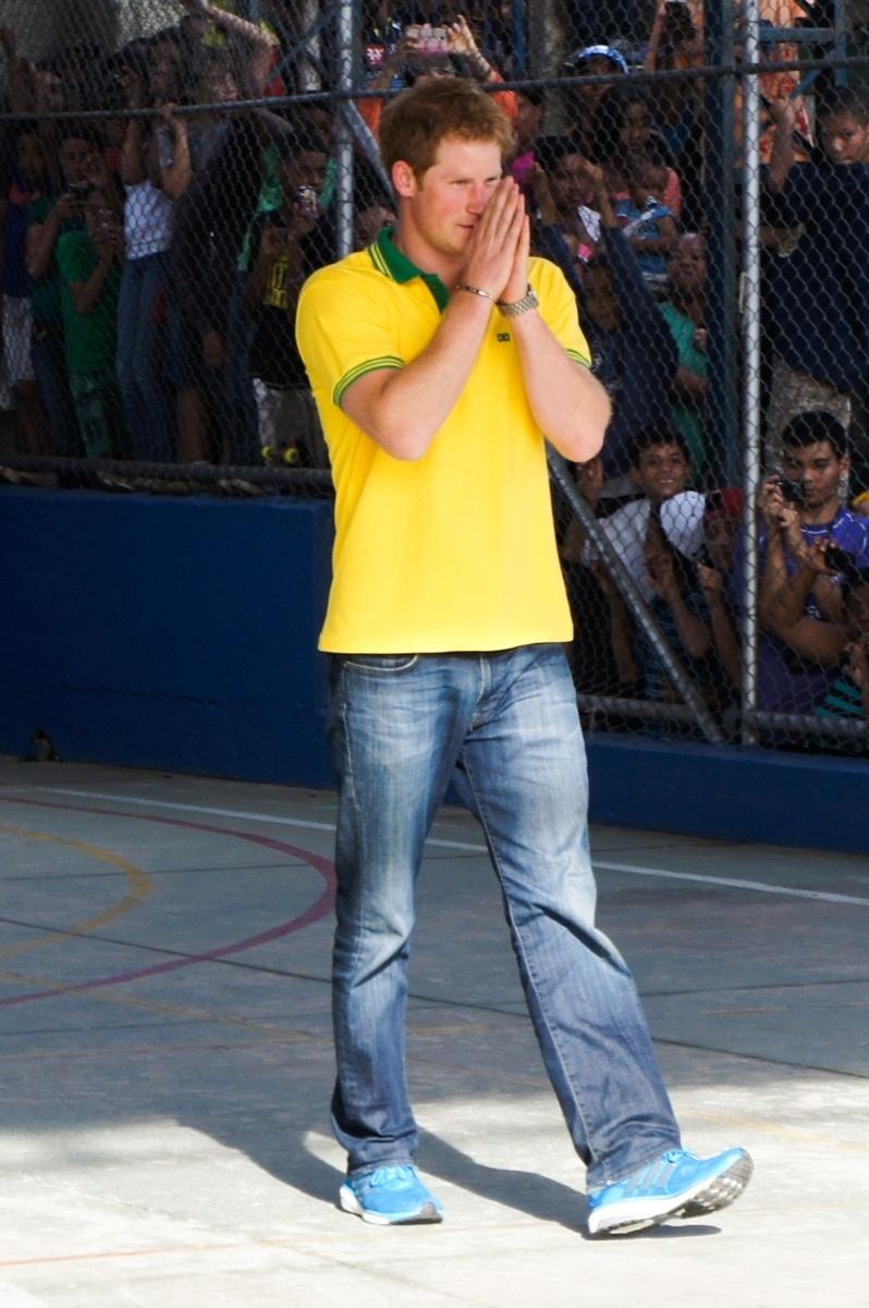 25.jun.2014 - Com a camisa do Brasil, Príncipe Harry joga futebol com crianças de projeto social em Diadema