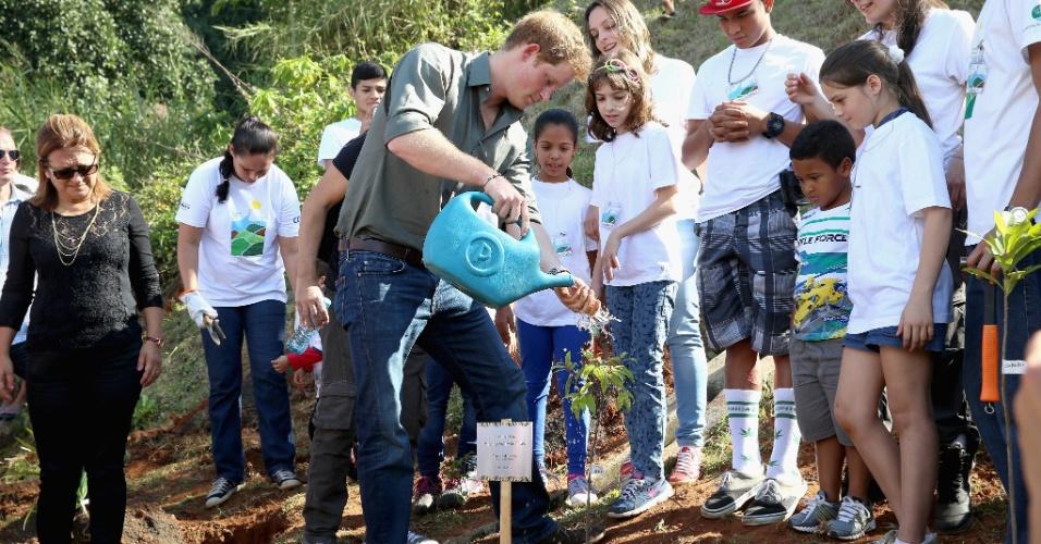 25.jun.2014 - Na frente de várias crianças, Príncipe Harry rega muda de árvore que plantou durante visita à Comunidade Cota 200, em Cubatão, no litoral de São Paulo