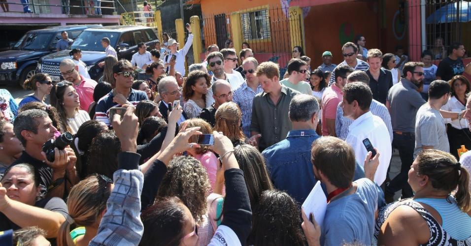 25.jun.2014 - Príncipe Harry é cercado por multidão ao visitar a Comunidade Cota 200, em Cubatão, no litoral de São Paulo