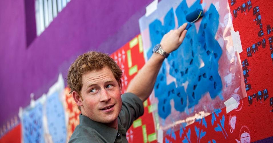 25.jun.2014 - Príncipe Harry pinta muro de uma casa durante visita à Comunidade Cota 200, em Cubatão, no litoral de São Paulo
