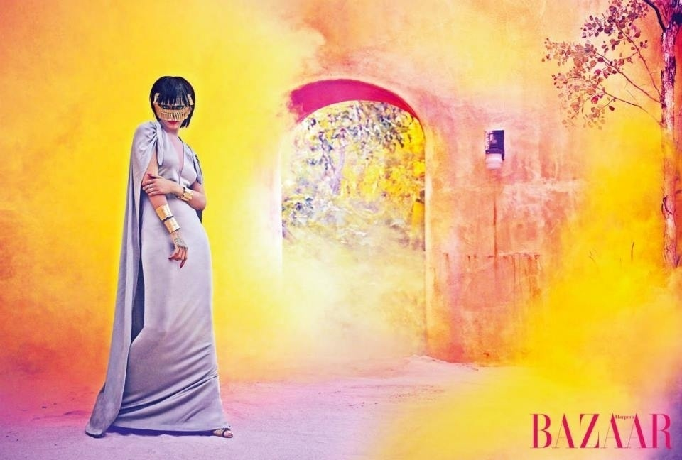 25.jun.2014 - Com parte do rosto coberta por acessório, Rihanna aparece com vestido longo comportado em ensaio da edição de julho/agosto da