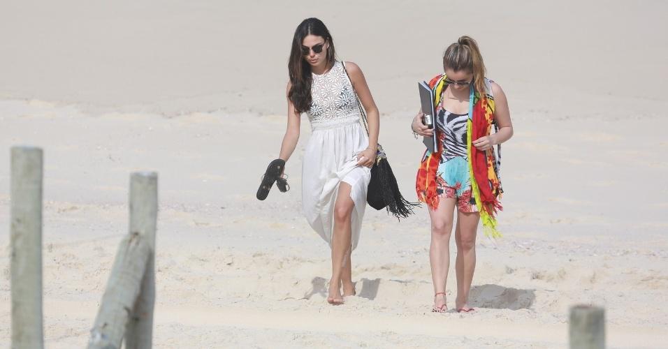 26.jun.2014 - Isis Valverde e amiga deixam a praia da Reserva, no Rio de Janeiro, após tomarem sol. A atriz usava um vestido longo e branco