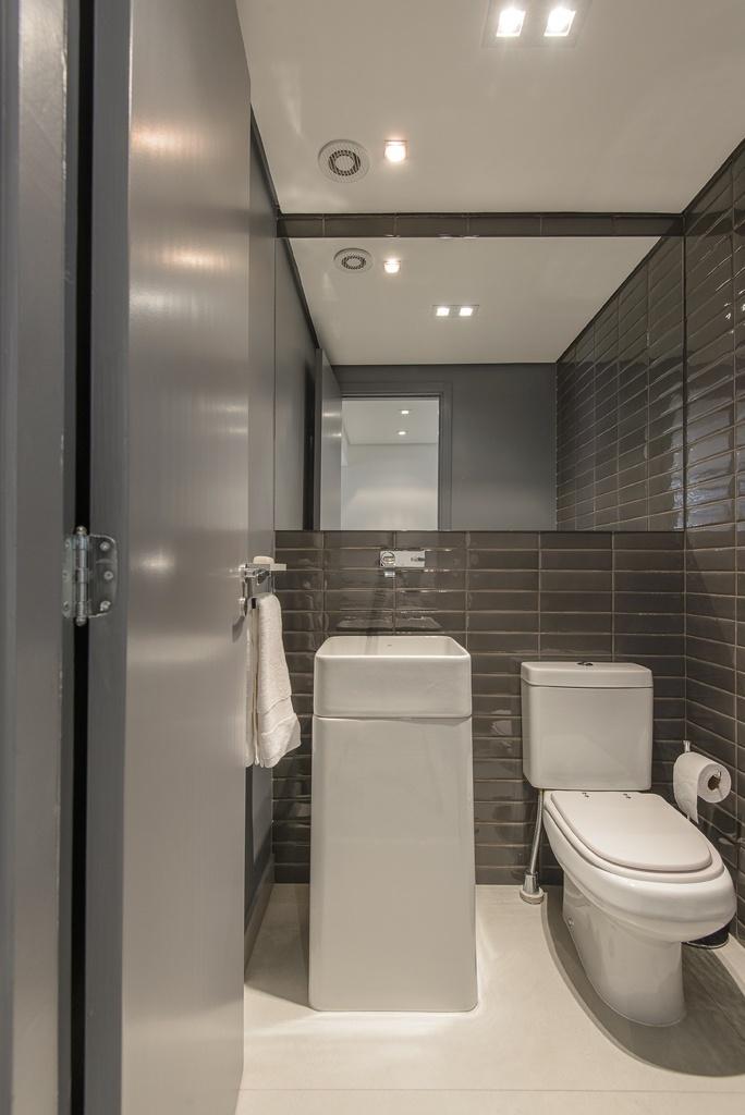 O lavabo decorado pelo escritório D2N acompanha a cartela de cores do projeto do apartamento, recebendo assim cerâmica vintage cinza chumbo para o revestimento da parede, de modo a destacar as louças sanitárias. Veja que o espelho ajuda a clarear o ambiente