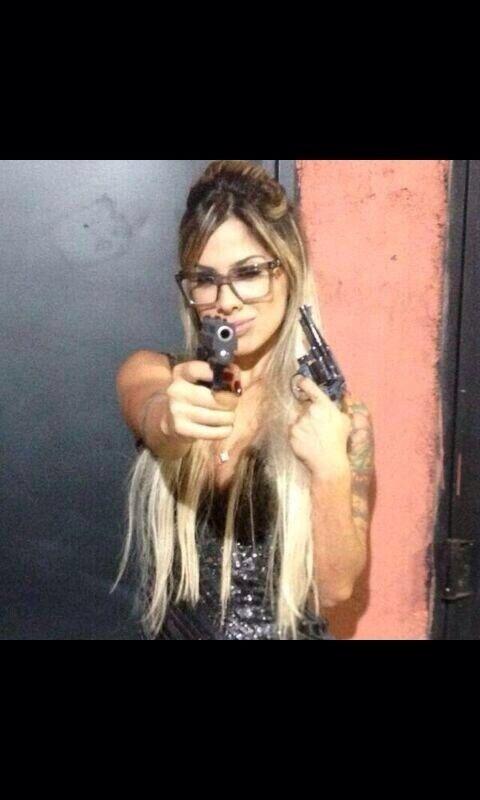 Ex-BBB Vanessa Mesquita posa segurando duas armas