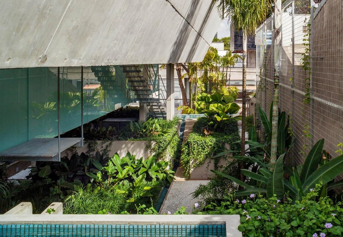 O paisagismo exuberante assinado por Raul Pereira quebra a rigidez do concreto estendendo-se por todo o comprimento do terreno até a rua. Ao fundo, a escada metálica passa entre as