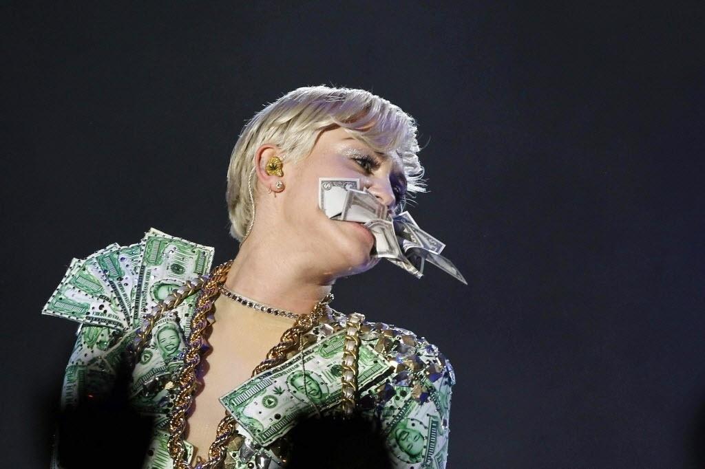 17.jun.2014 - Miley Cyrus morde notas de dinheiro durante show da turnê Bangerz no Palacio de los Deportes de Madri, na Espanha
