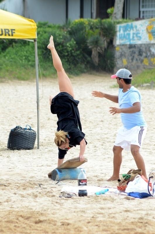 10.jul.2014 - Carolina Dieckmann ensaia para plantar bananeira na praia de Geribá, em Búzios (RJ)