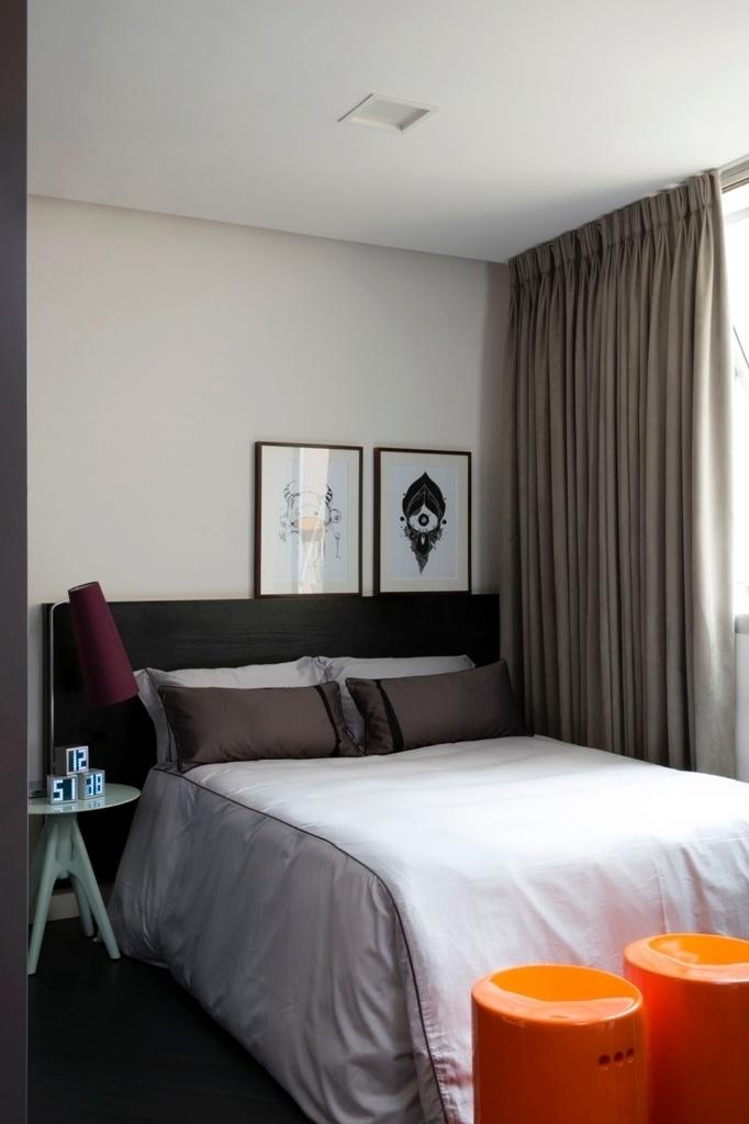 No dormitório, a marcenaria em MDF (Contexto Oficina da Madeira) para cabeceira acompanha o material usado no armário que fica embutido e escondido na parede à esquerda. A mesa lateral, em madeira laqueada da Clami Design, e os bancos em cerâmica esmaltada, além de
