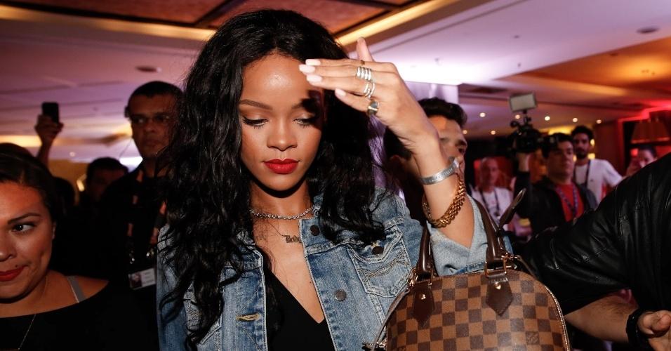 11.jul.2014 - Rihanna deixa o hotel em Copacabana cercada por seguranças. A cantora coloca a mão no rosto para evitar os flashes