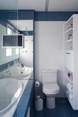 Através do espelho colocado em frente à banheira é possível ver o box com dois chuveiros para o casal (à esq.). As pastilhas de vidro azuis, da Bisazza, comparecem no contorno da banheira. Destaque para a televisão instalada no espelho. O apê FMS tem projeto de reforma do escritório KTA Arquitetura