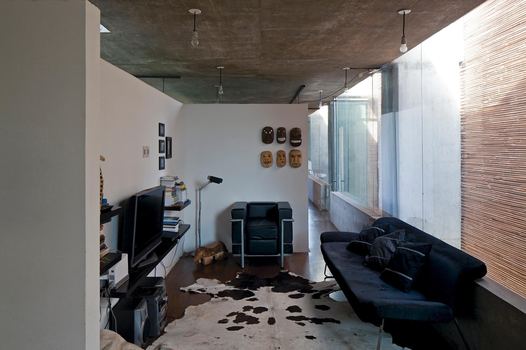 A divisão interna entre ambientes se dá em alvenaria cerâmica, formando paredes que não alcançam o forro de concreto aparente. Os pisos reaproveitam a madeira utilizada nas fôrmas de concretagem, lixadas e tingidas e o vão sul (à dir.), com 16 m de comprimento, volta-se para as caixas-contrapeso onde estão as áreas de serviços e de circulação vertical. A arquitetura é do escritório TDA, para residência em Luque, no Paraguai