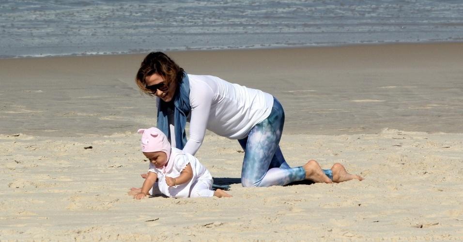 23.jul.2014 - A atriz Guilhermina Guinle brinca com a filha Minna, que usa um gorro de bichinho, na praia de Ipanema, na zona sul do Rio
