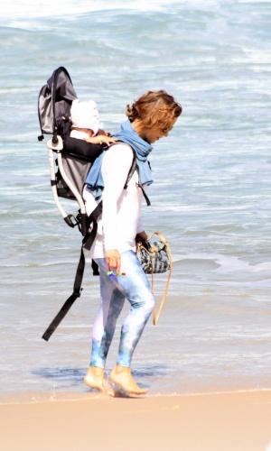 23.jul.2014 - Com a filha Minna nas costas, Guilhermina Guinle passeia na praia de Ipanema, na zona sul do Rio