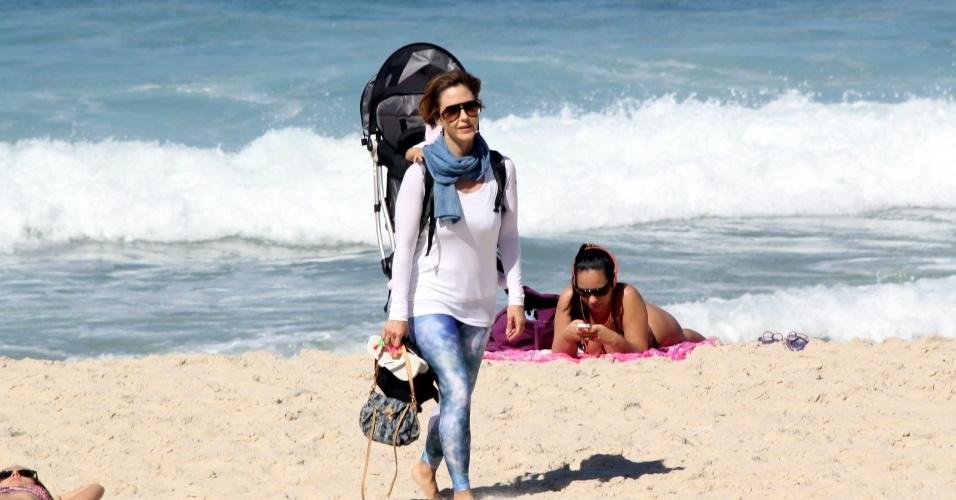 23.jul.2014 - Com a filha Minna nas costas, Guilhermina Guinle passeia na praia de Ipanema, na zona sul do Rio. A menina, de dez meses, é fruto da relação da atriz com o advogado Leonardo Antonelli, irmão da atriz Giovanna Antonelli