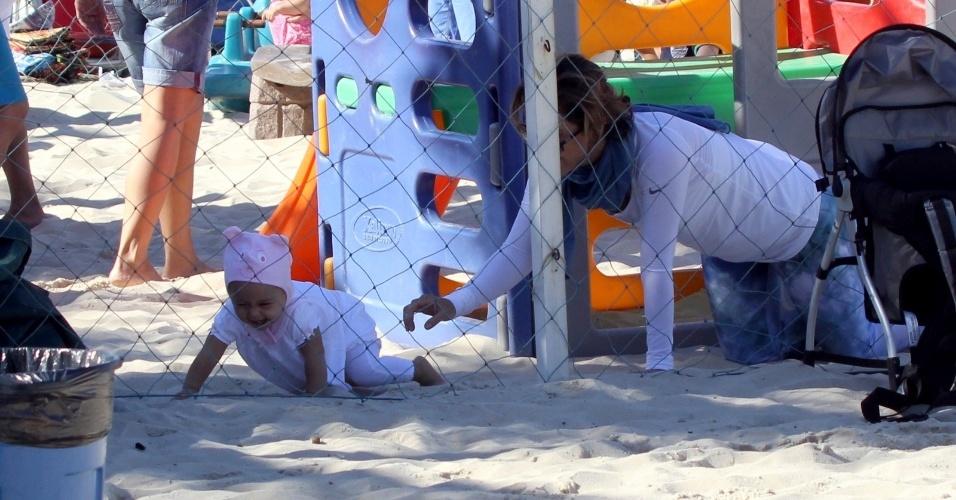 23.jul.2014 - Guilhermina Guinle brinca de pegar a filha Minna, que usa um gorro de bichinho, no parquinho infantil da praia de Ipanema, na zona sul do Rio
