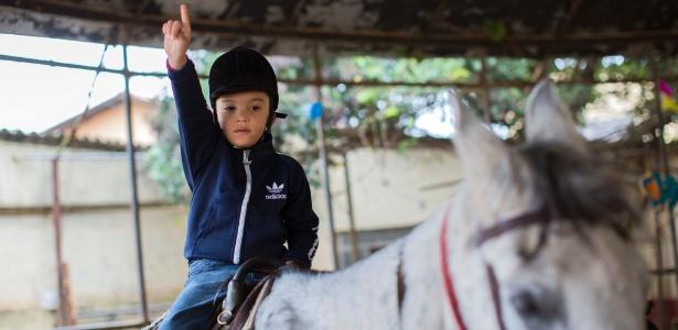 Arthur Silva Nascimento, de seis anos, durante sessão de equoterapia
