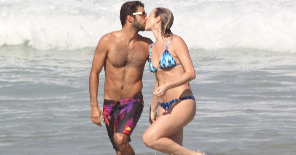 1.ago,2014 - Luana Piovani e o marido Pedro Scooby se beijam ao sair do mar na praia do Leblon