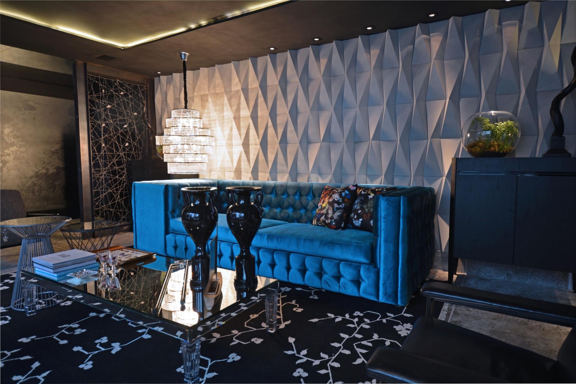 Rogério Pandolfo assina o living Liberte-se e Dê Asas a sua Imaginação. No ambiente, o preto e o cinza predominam nas peças e acabamentos, com exceção do tom azulado do sofá. Atrás do móvel, o painel cimentício (Castelatto) em relevo