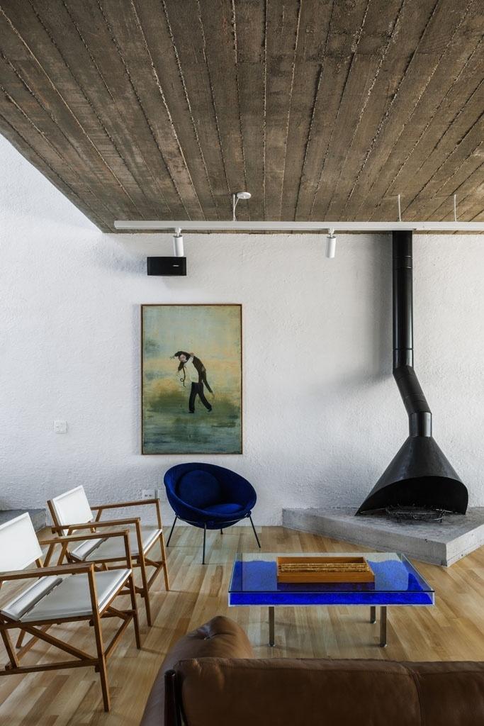 As duas cadeiras à esquerda (Marcenaria Baraúna) são assinadas por Francisco Fanucci. E a poltrona azul Bowl, ao lado da lareira, tem design da arquiteta Lina Bo Bardi, madrinha do proprietário da Casa Pepiguari, em São Paulo. A arquitetura é assinada por Marcelo Ferraz, do escritório Brasil Arquitetura