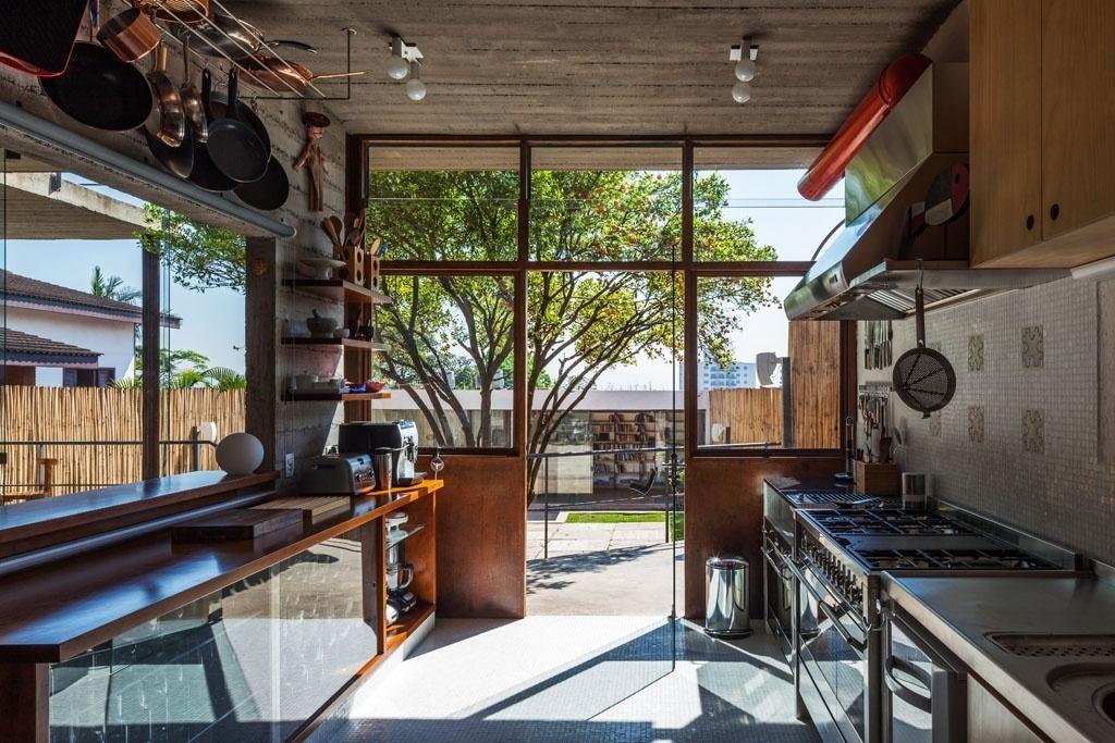 A  cozinha também está integrada à varanda e ao quintal. A parede sobre a área de cocção é revestida por pastilhas de vidro, com detalhe em seis azulejos de um antiquário português, nas cores azul e branca. A cozinha é profissional, com bancada e eletrodomésticos em aço inox. A marcenaria em ipê do mobiliário tem cor muito próxima à do próprio aço dos caixilhos (à frente). A Casa Pepiguari foi projetada por Marcelo Ferraz e fica em São Paulo