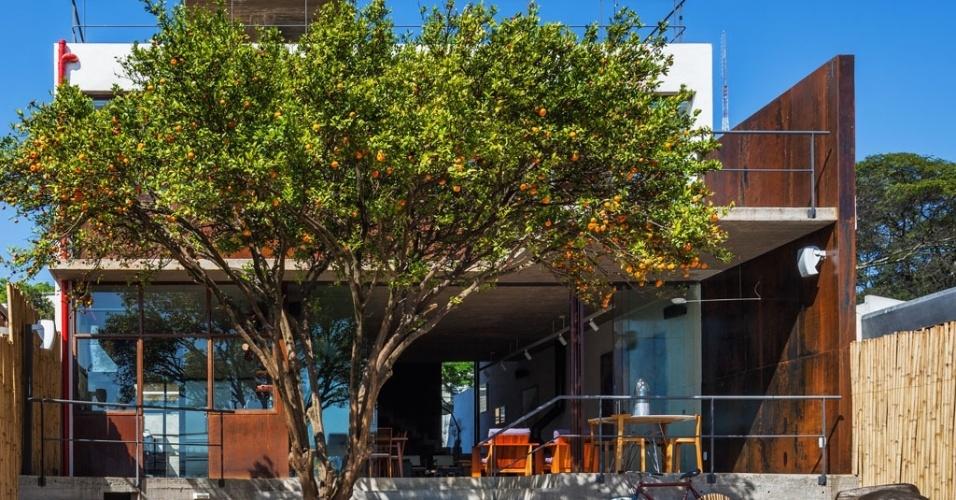 Vista a partir dos fundos da Casa Pepiguari, em São Paulo, a laje dá apoio a duas caixas d'água e é sustentada pela mesma parede estrutural que divide as funções social e de serviços, desde o pavimento térreo, alongando-se da entrada da rua até o final da sala de estar. A caixilharia foi desenvolvida pelo escritório Brasil Arquitetura em aço corten (liga de aço, nióbio e cromo)