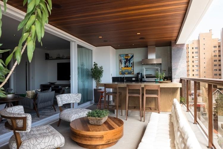 Ligada ao living, a varanda do apartamento em Campinas (SP) tem churrasqueira com balcão e banquetas para acomodar os convidados. Para o ambiente, a arquiteta Elaine Carvalho ainda projetou um espaço de estar, decorado com banco e almofadas futon e poltronas (Artzzi) de estilo