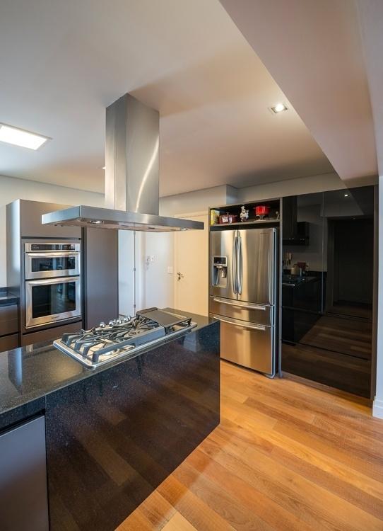No apartamento em Campinas (SP), a cozinha tem piso em madeira de demolição e bancada de granito preto. O móvel (Kitchens) onde está embutida a geladeira é composto por armários revestidos por laminado melamínico. A arquiteta Elaine Carvalho assina o projeto de interiores do imóvel