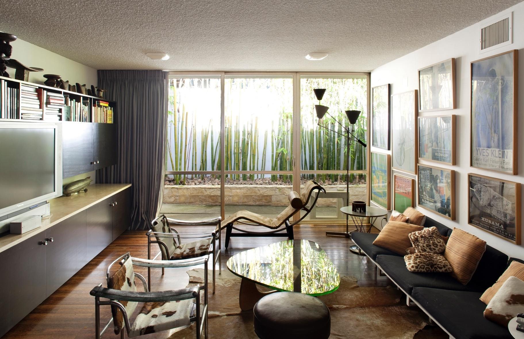 A sala de TV da Strick House possui portas de correr de vidro, típicas da arquitetura modernista dos anos de 1950 e 1960. Com caixilharia metálica, a proposta integra interiores a um paisagismo inspirado na obra do brasileiro Roberto Burle Marx. A composição é de vegetação tropical na residência que fica em Santa Mônica, Califórnia, e foi projetada por Oscar Niemeyer em 1964