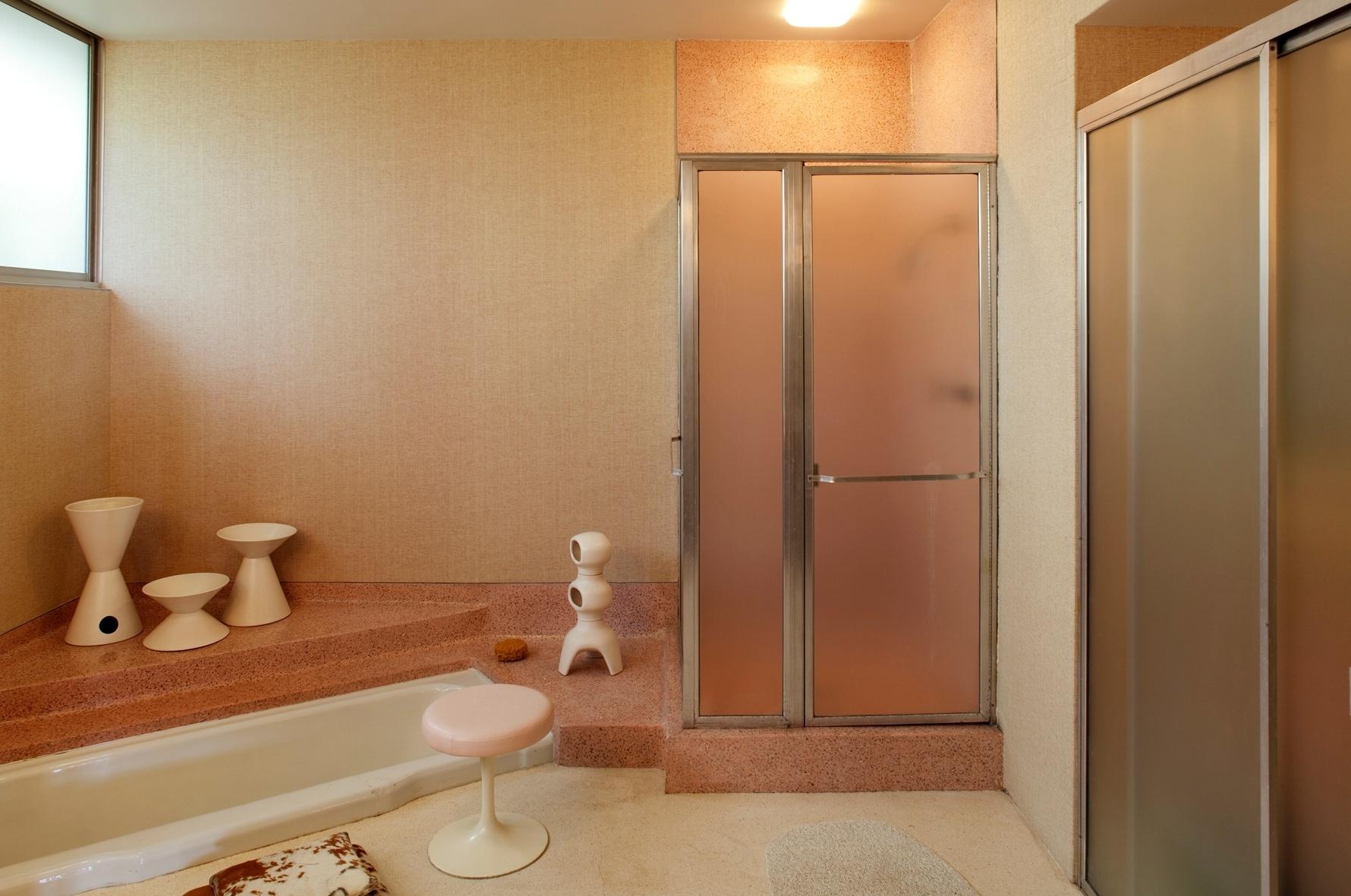 O estilo sessentista está no piso e paredes em granilite cor de rosa para o chuveiro e a banheira. O restante do chão levou  granilite bege claro. O banco Saarinen é um dos exemplos de uma quase obsessão do proprietário, o restaurador e arquiteto Michael Boyd, por elementos modernistas. A casa Joseph Strick tem arquitetura de Oscar Niemeyer e fica em Santa Monica, na Califórnia