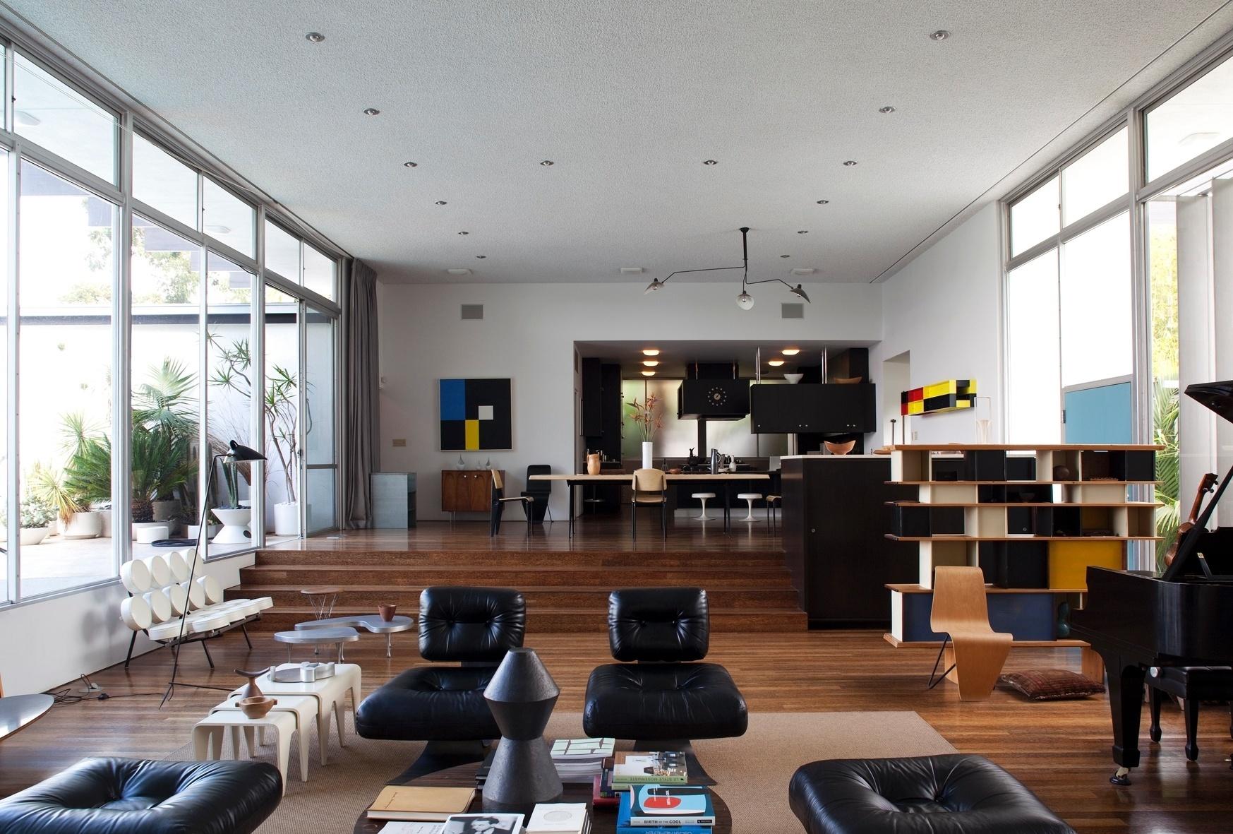 A cozinha, ao fundo, é integrada à área de convivência da Strick House. A sala, com 68 m de comprimento, divide-se em estar e jantar e é completamente envidraçada. O piso apresenta um elemento brasileiro: a madeira de palmeira. O projeto da residência na Califórnia é de Oscar Niemeyer, datado de 1964. Todavia, o arquiteto não participou da construção da casa, mas aprovou tanto o resultado da obra original, quanto o último restauro promovido pelo designer Michael Boyd, atual proprietário