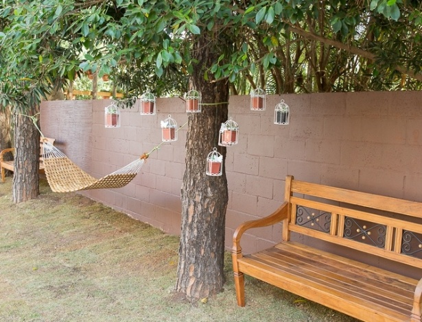 Para criar um ambiente romântico, decore as árvores com vasinhos pendentes ou mesmo castiçais com velinhas réchaud (só tome cuidado com a altura, para não colocar fogo na planta!). Esse simples cuidado deixa a área de descanso do jardim ainda mais aconchegante. Na foto, o espaço Jardim no Quintal, assinado pela arquiteta Cláudia Schutzer de Magalhães para a Mostra de Paisagismo da edição 2014 da Expoflora, em Holambra (SP)