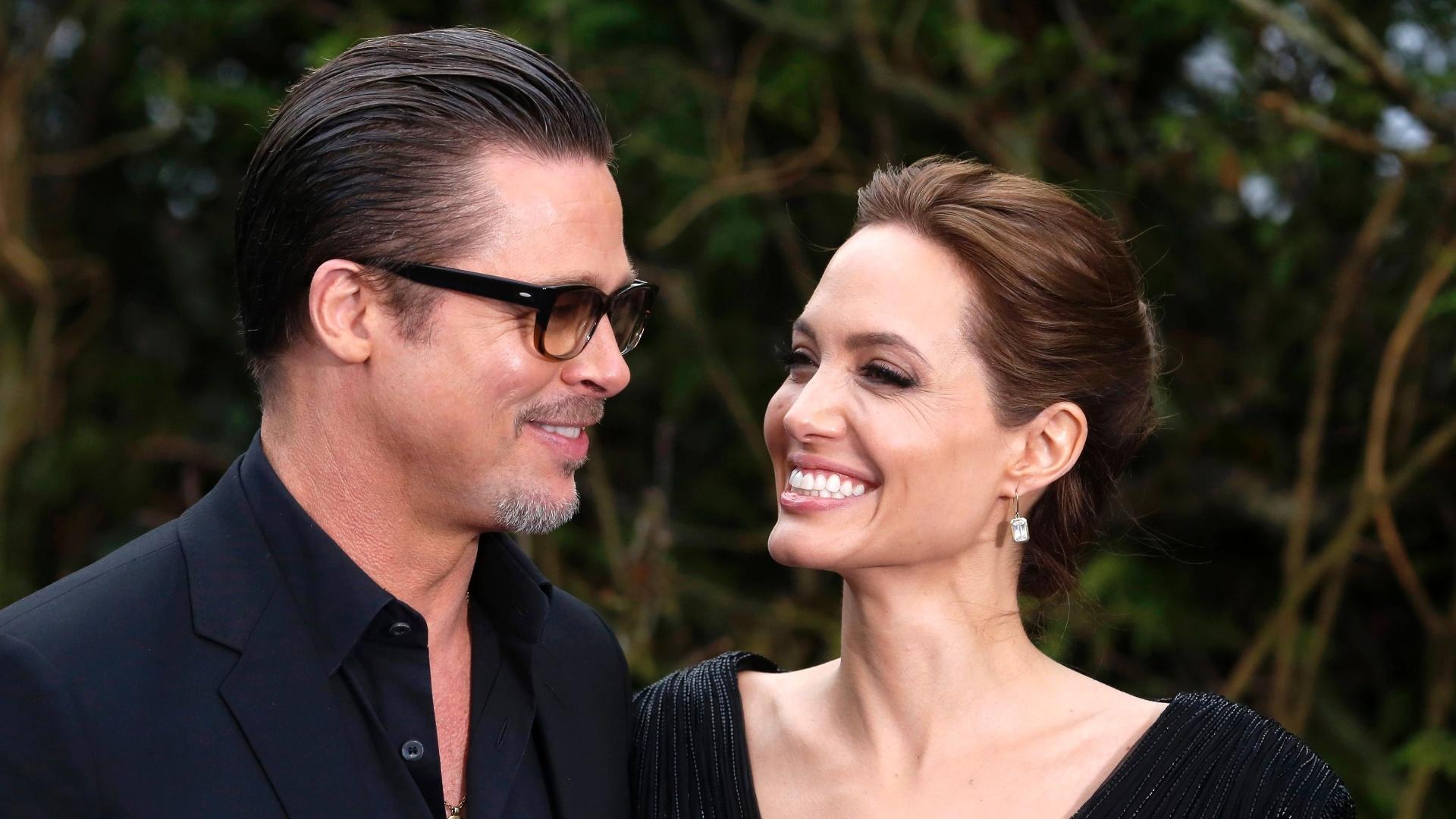 8.mai.2014 - Brad Pitt e Angelina Jolie sorriem ao chegar para exibição dos figurinos de