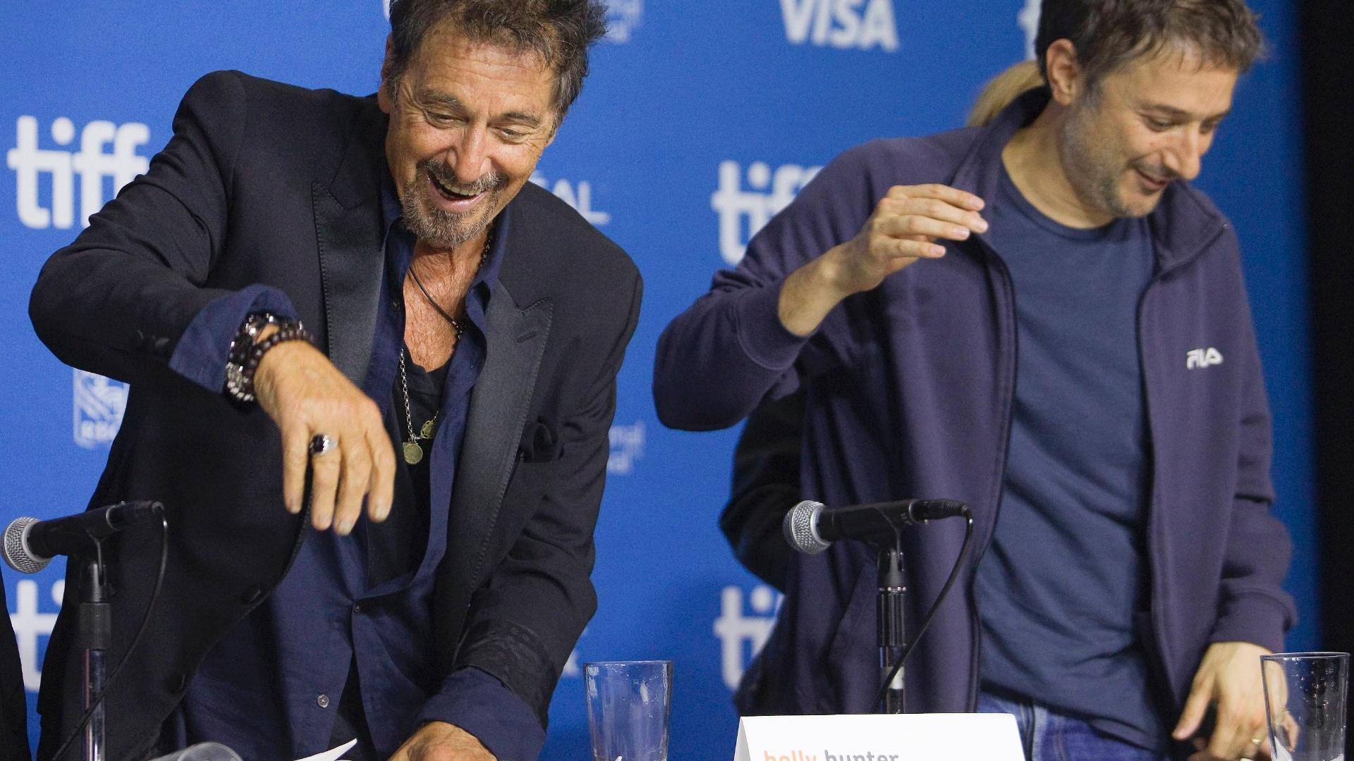 07.set.2014 - Al Pacino e Harmony Korine limpam a mesa após o ator derrubar água durante coletiva de imprensa para promover o filme
