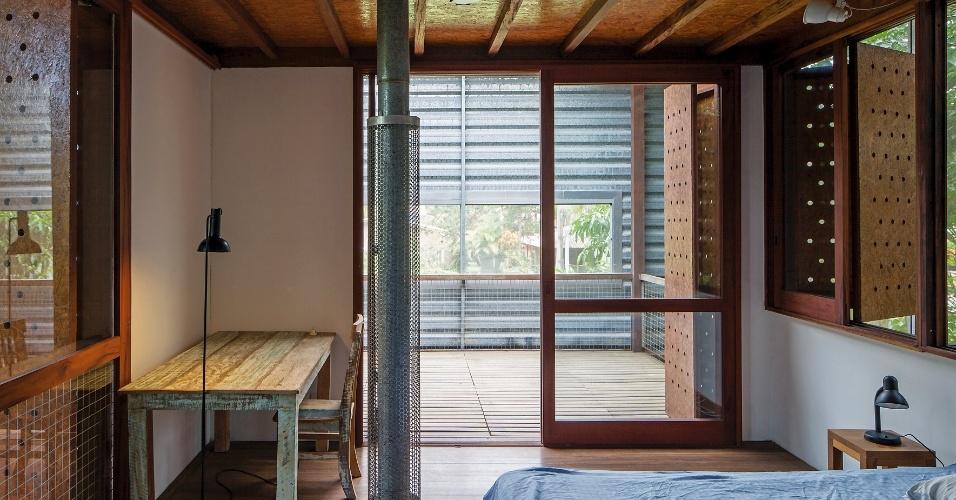 No dormitório do casal a sensação de aconchego é dada pela madeira cumaru e pelo compensado OSB das portas. Nelas há perfurações redondas que permitem a ventilação a partir do deck de madeira. A
