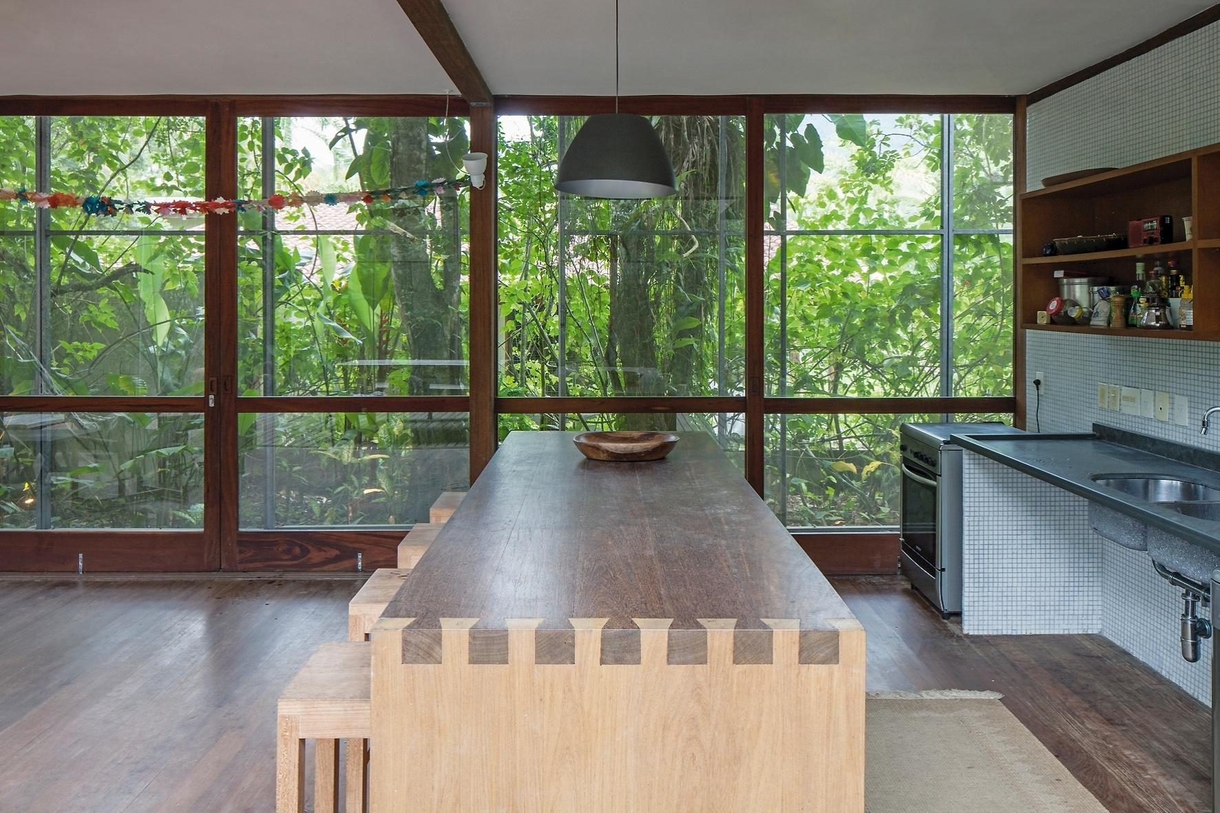 O espaço de jantar é totalmente integrado à cozinha e voltado para o exterior, onde impera a presença da Mata Atlântica. O mobiliário escolhido pelos proprietários expressa simplicidade, de acordo com a proposta descontraída da Casa RR, projetada pelo escritório Andrade Morettin