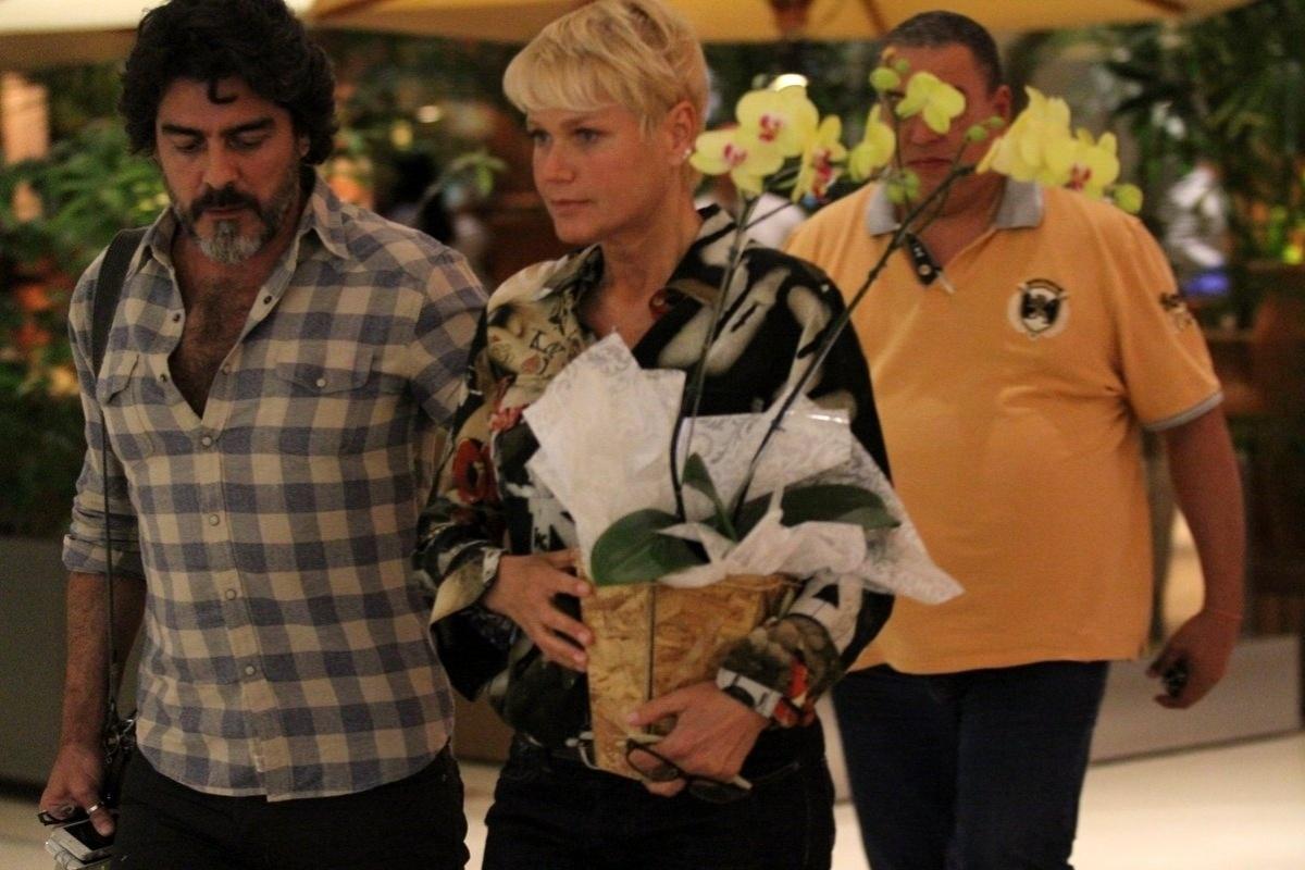 11.set.2014 - Segurando um vaso de orquídeas, Xuxa é vista passeando em shopping com o namorado, Junno
