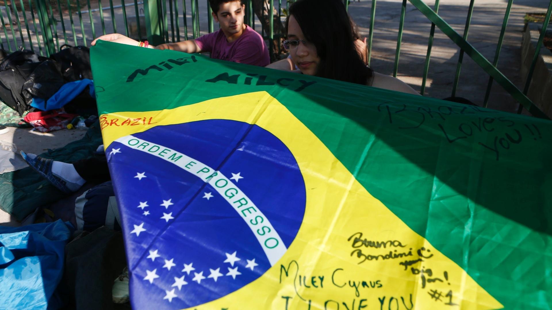 22.set.2014 - Garota estende bandeira do Brasil assinada que será entregue para Miley Cyrus