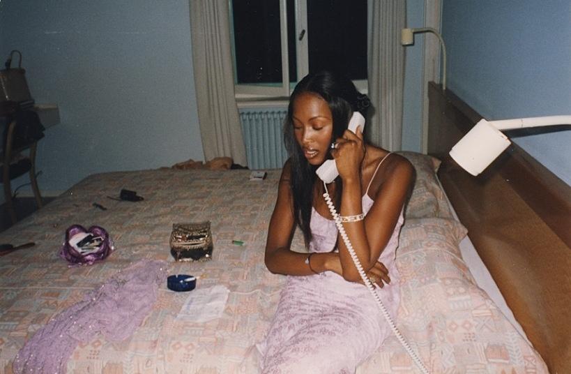 Em um possível quarto de hotel, a modelo Naomi Campbell falando ao telefone