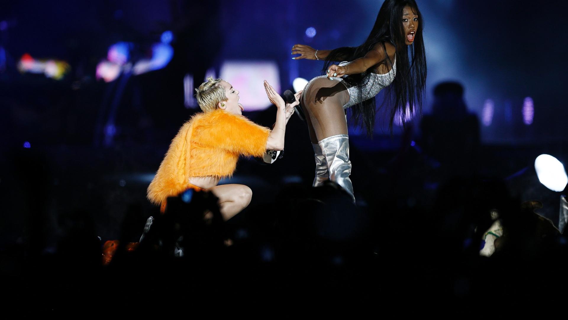 26.set.2014 - Miley Cyrus bate na bunda de dançarina durante show no Anhembi, em São Paulo; a cantora traz sua turnê Bangerz ao Brasil