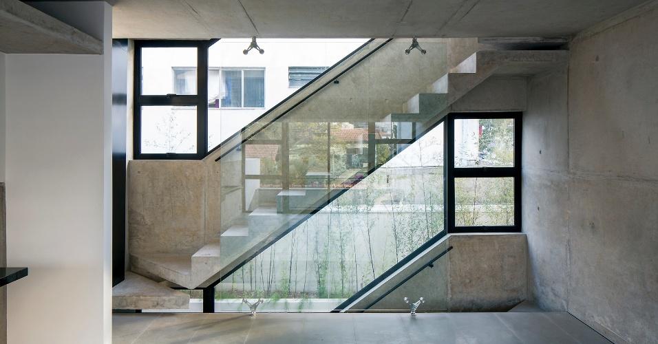 As escadas de ligação entre os andares do Vila Aspicuelta, projetado pelo escritório Tacoa Arquitetos, possuem, de um lado, guarda-corpo estrutural de concreto e, de outro, pano de vidro sustentado por ferragens articuladas (