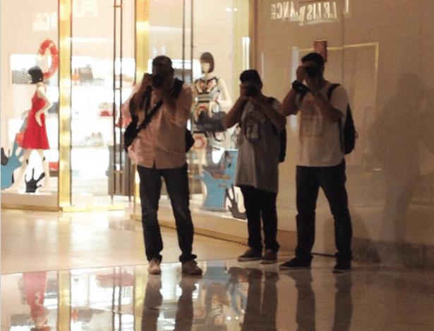 3.out.2014 - Carol Nakamura se diverte fotografando paparazzi com seu próprio celular dentro de um shopping.