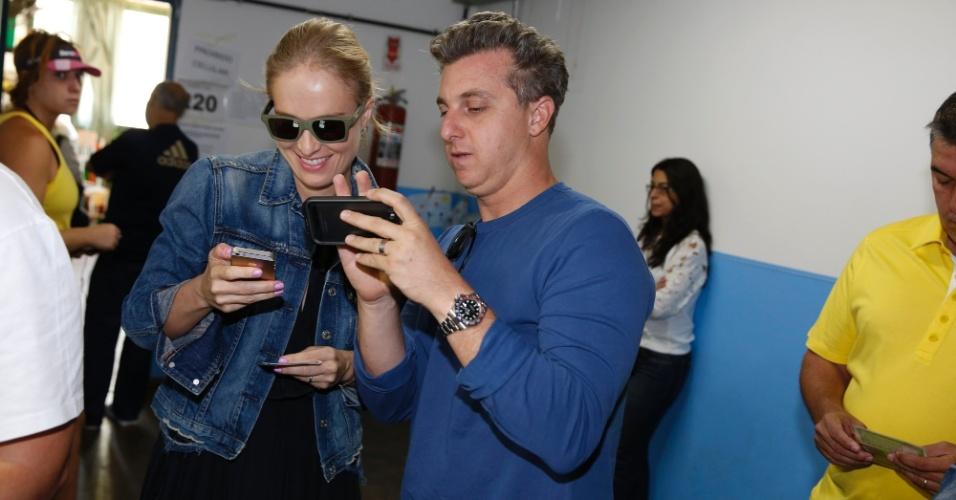 5.out.2014 - Angélica e Luciano Huck entram na zona eleitoral com celular nas mãos
