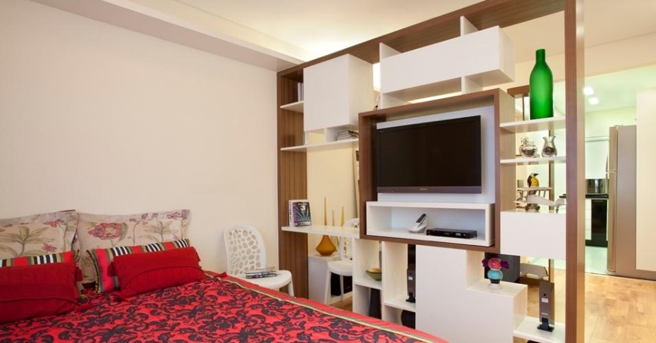 No apartamento decorado por Adriana Fontana, o quarto é delimitado pela estante vazada. O ambiente ganha privacidade, mas permanece integrado ao estar. Na porção central do móvel, o rack para a TV é pivotante e oferece acesso à tela tanto no dormitório (foto), quanto na ala social