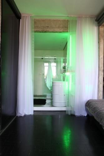 Detalhe do espaço do banheiro, delimitado por uma fluida cortina, no apartamento Bohemian Cyborg, assinado por Guto Requena