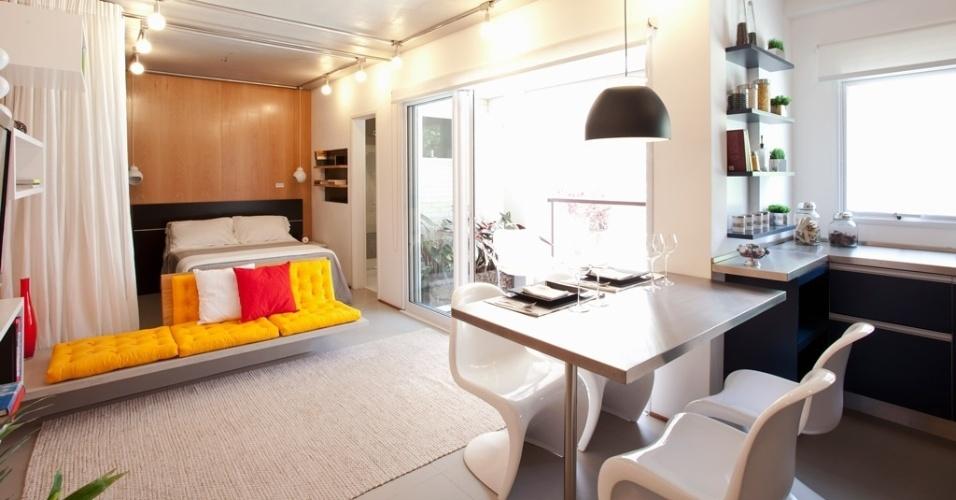 O sofá de alvenaria coberto por futons amarelos não impede a integração dos ambientes, mas marca a separação da área do dormitório, que pode ser isolada do estar pela cortina branca (na foto, recolhida à esquerda). O projeto do Estúdio Option é assinado pelo escritório FGMF