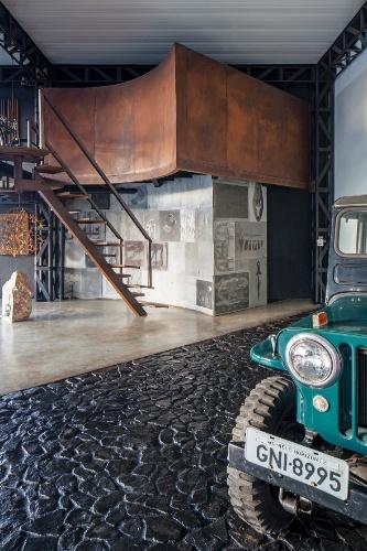 Os espaços de estar - que também é ocupado pelos jipes - é bastante inusitado, com dois tipos de piso: concreto e pedras locais pintadas de preto. Ao fundo, as paredes do lavabo foram revestidas com chapas litográficas usadas e encimadas pelo banheiro do casal em linhas curvas, no mezanino. Destaque para a escada tipo Santos Dumont, com degraus alternados, que gira 180°