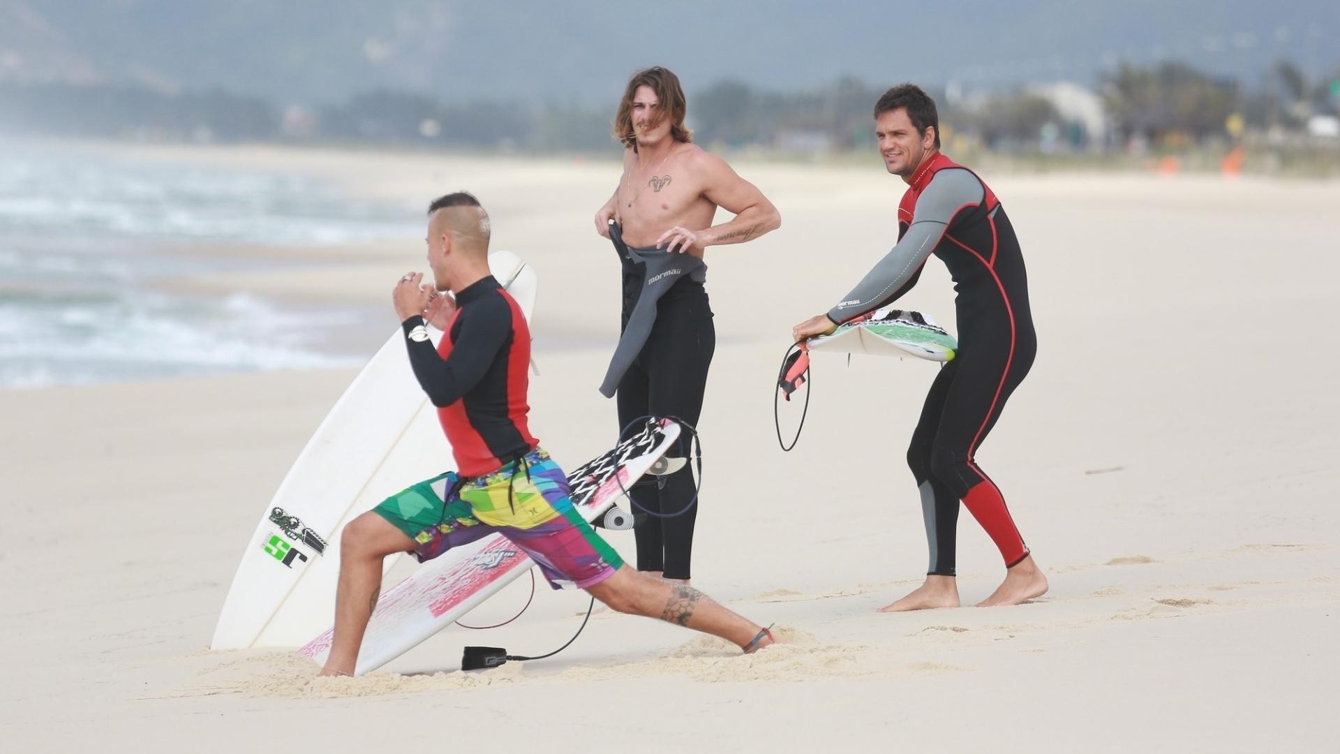 23.out.2014 - Na praia da Reserva, Paulinho Vilhena se alonga ao lado de Rômulo Neto e amigo na areia, antes de surfar