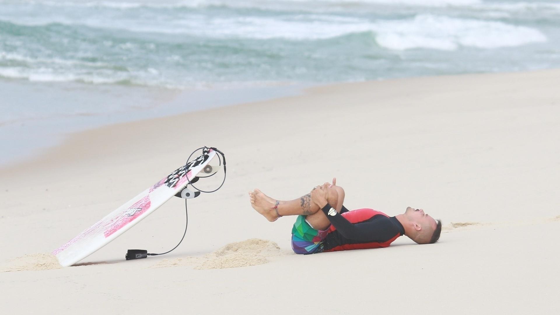 23.out.2014 - Paulinho Vilhena se alonga na areia antes de surfar na praia da Reserva, no Rio.